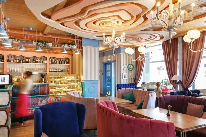 Барная стойка в виде огромных книг и нестандартный декор под потолком усиливает схожесть с «Зазеркальем»